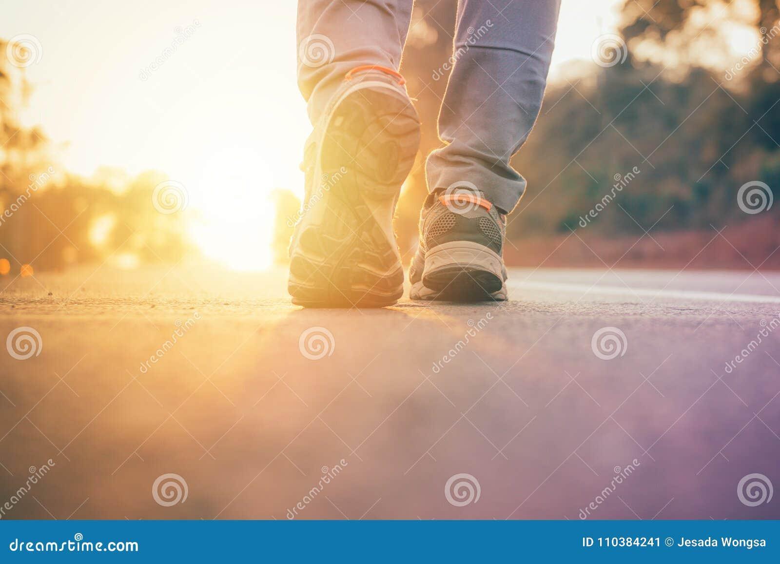 De mens die op weg met zon lichte gloed lopen, sluit omhoog op de trainingwellness van de schoenjogging na het werk