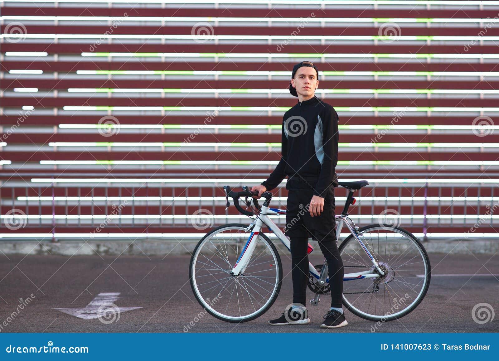 De mens in donkere sportkleding en met fietsenrekken op de gestreepte achtergrond van het grote scherm en bekijkt de camera