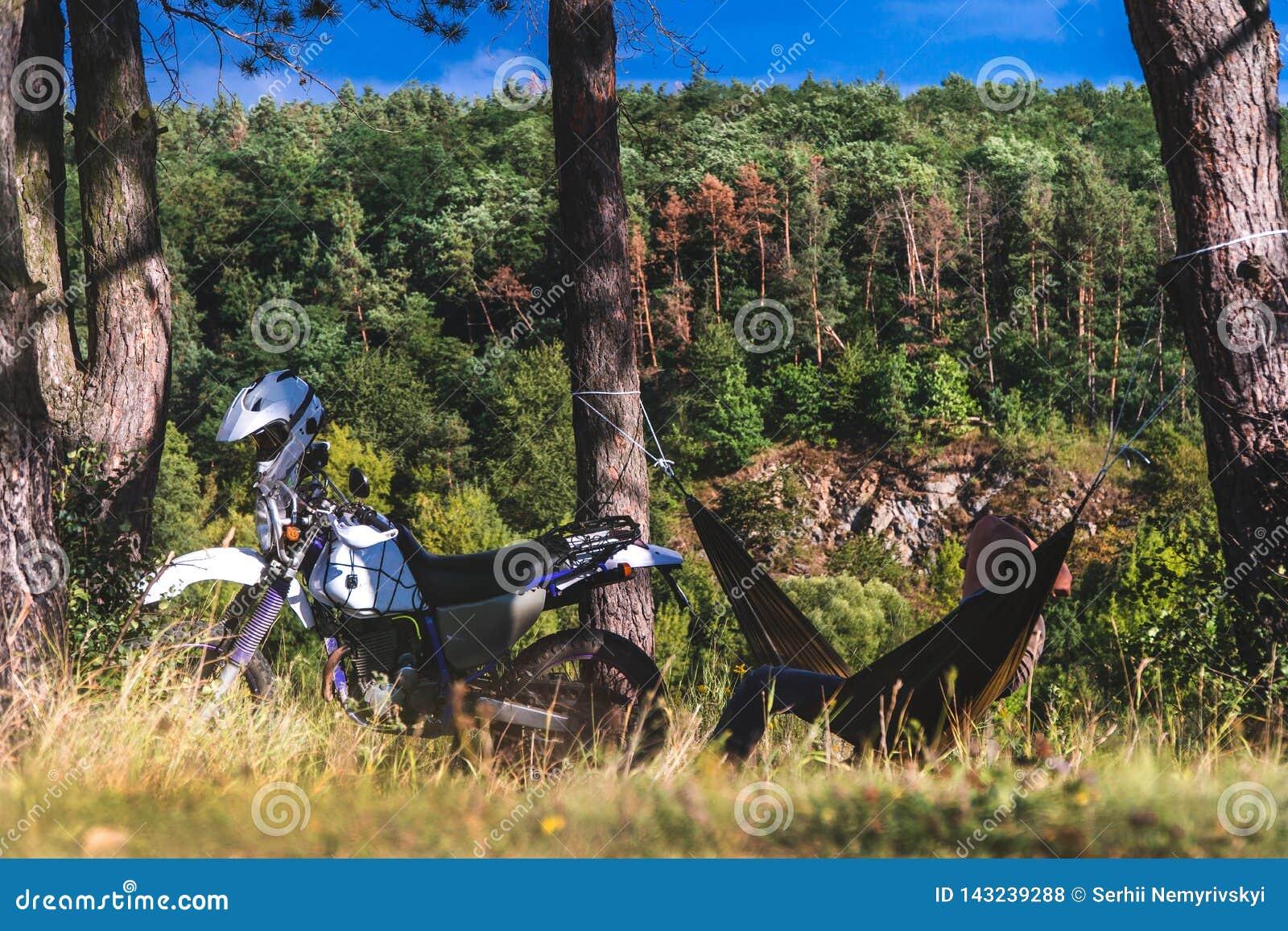 De mens in een hangmat op pijnboom bosberg, openluchtreiziger ontspant, enduro van wegmotorfiets