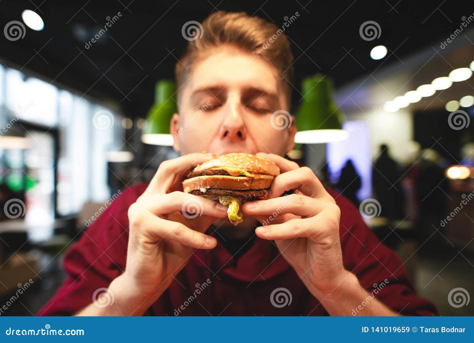 De mens eet een heerlijke grote hamburger met zijn gesloten ogen en verrukkingen Close-upportret van een grappige mens die een ha