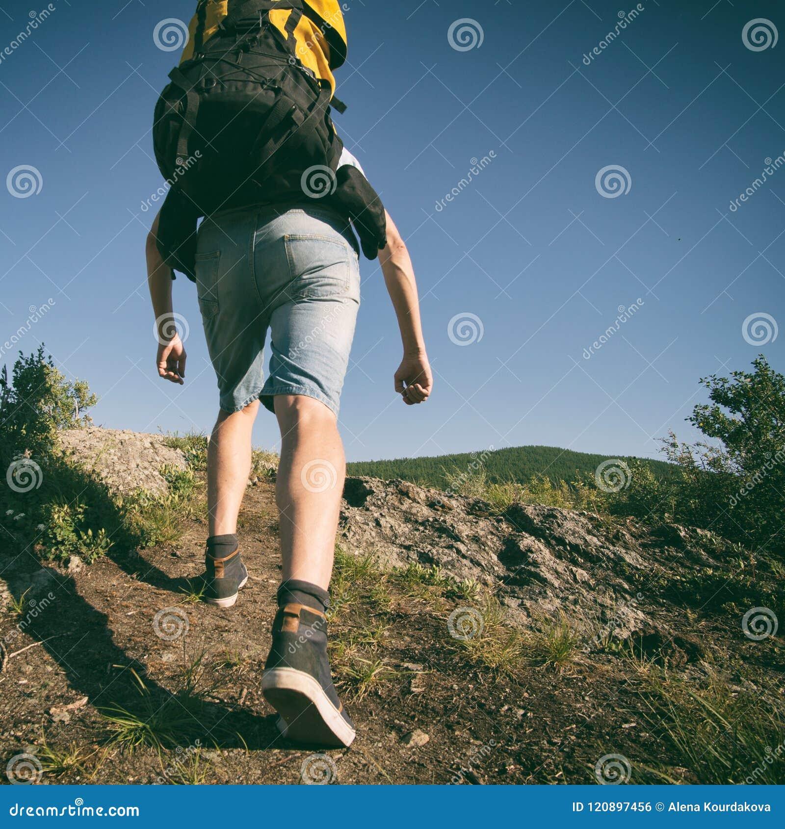 De mens gaat bergop met een rugzak op zijn rug