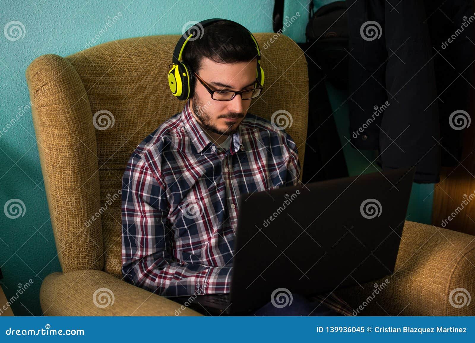 De mens gebruikt laptop op bank in zijn huis