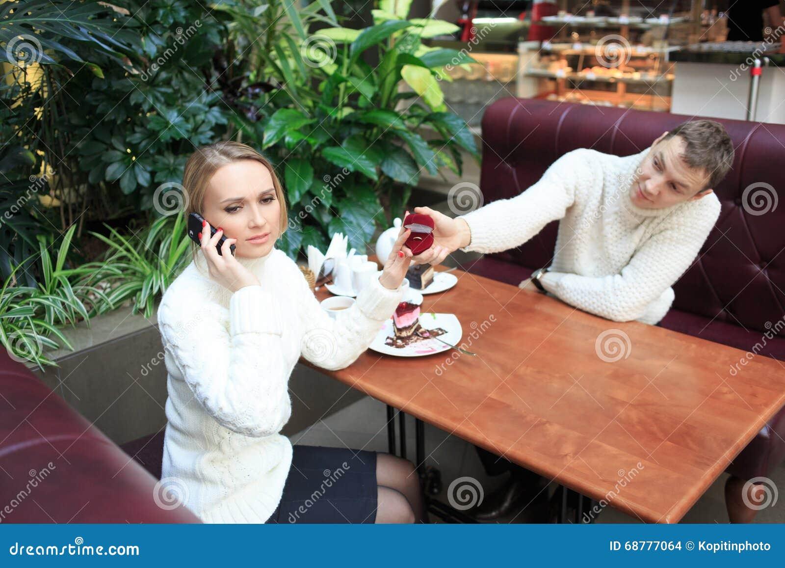 De mens geeft het meisje een ring Vrouw die op telefoon spreekt