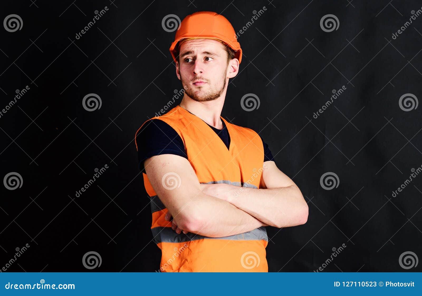 De mens in helm, de wapens van de bouwvakkergreep kruiste op borst, zwarte achtergrond Arbeider, contractant, bouwer op strikt ge