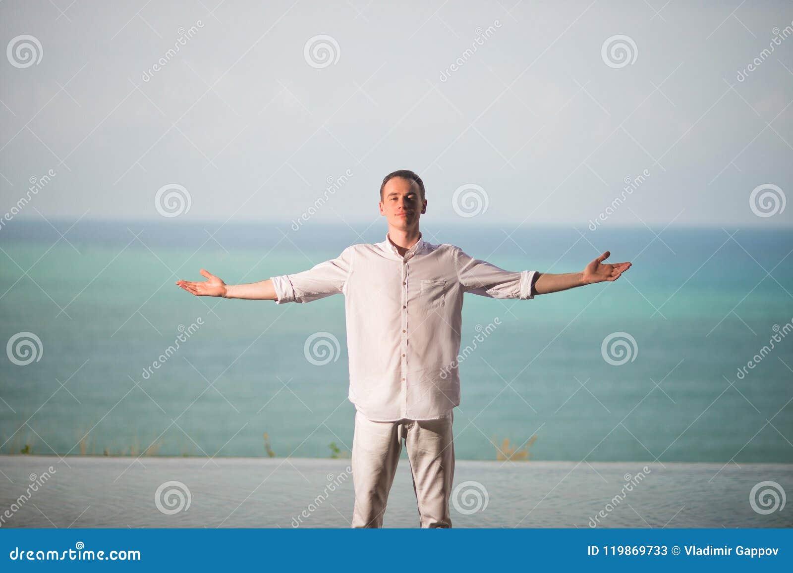 De mens in het wit kleedt status op een achtergrond van oceaan met gescheiden handen aan de kant, genietend van de vrijheid