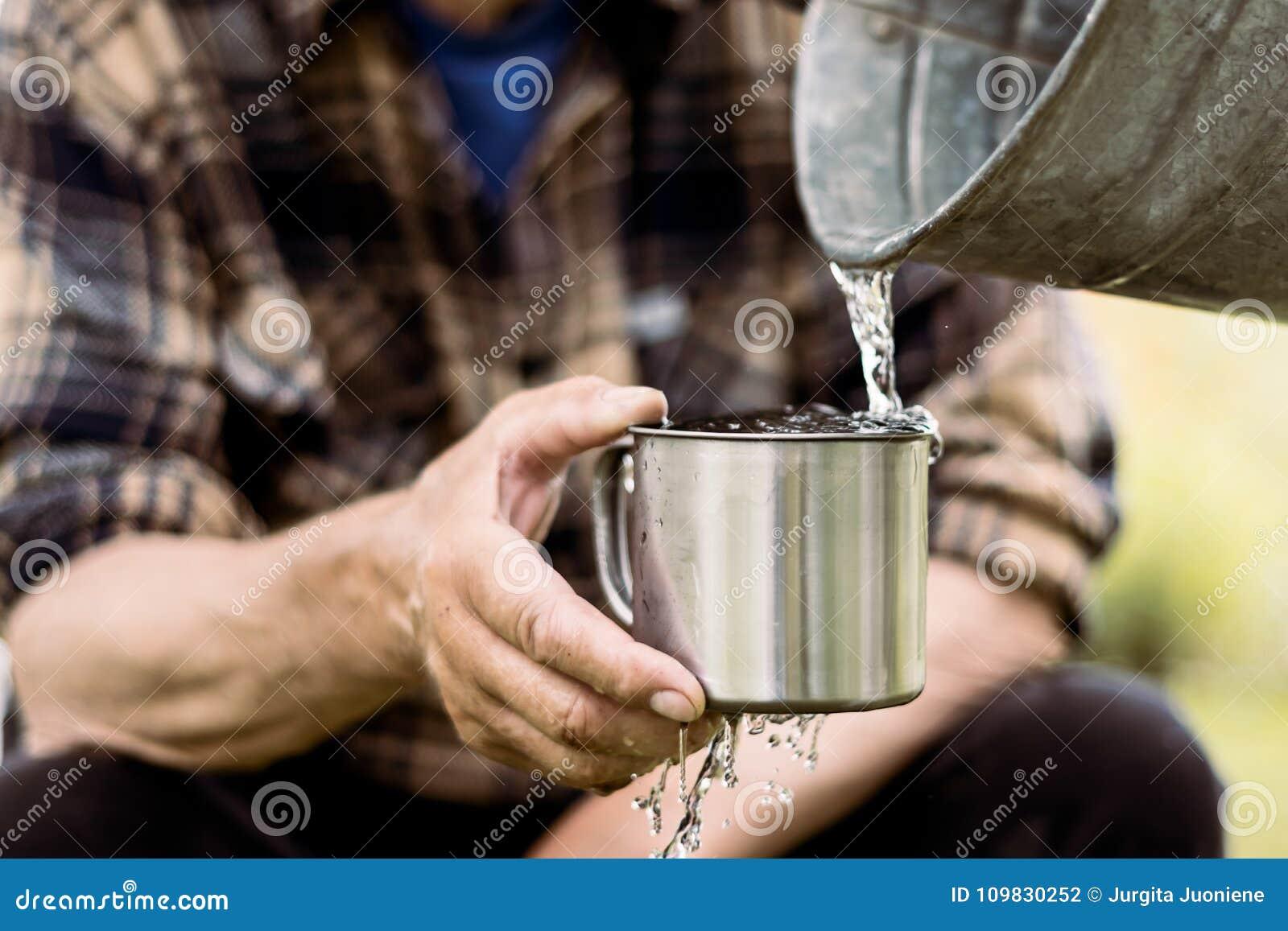 De mens houdt een staalmok en een bronwater giet van een emmer