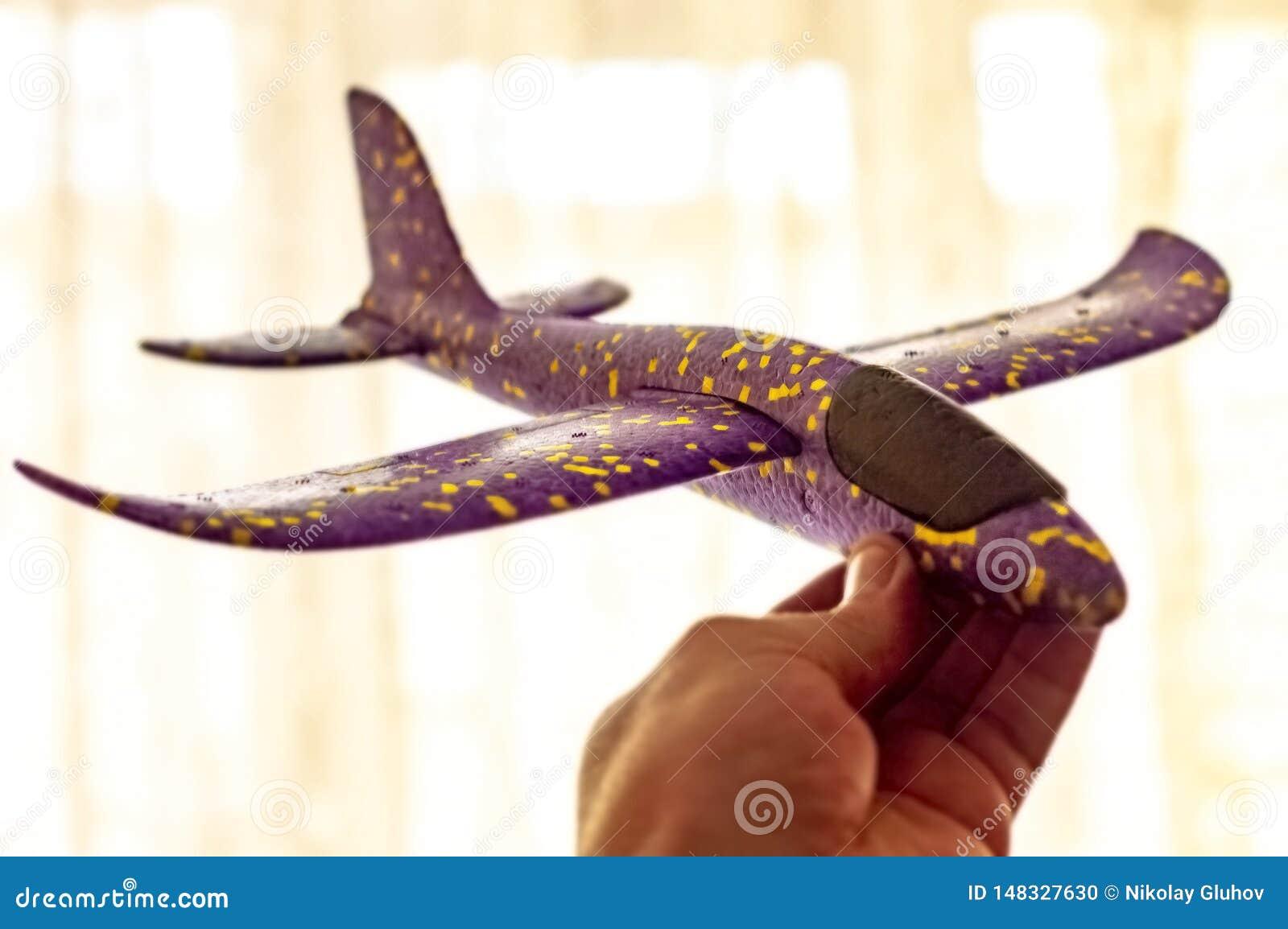 De mens houdt een vliegtuig en de dromen van kinderen plastic van het worden een loods Concept