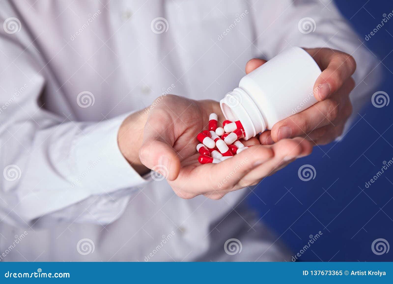 De mens houdt multi-colored pillen in handen De panacee, het leven sparen de dienst, schrijft geneesmiddel, wettelijke drogisteri