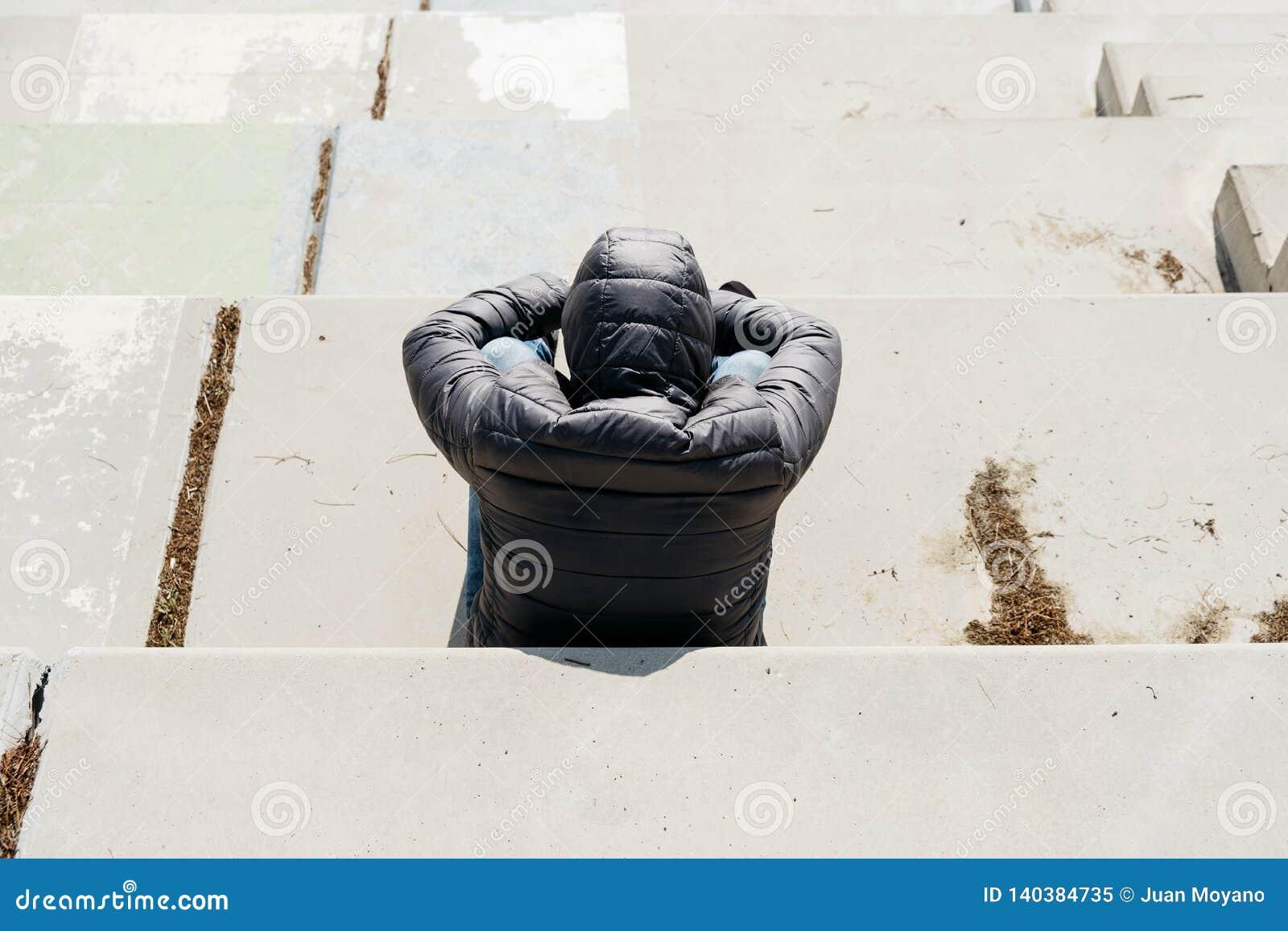 De mens krulde omhoog het zitten op een openluchttrap