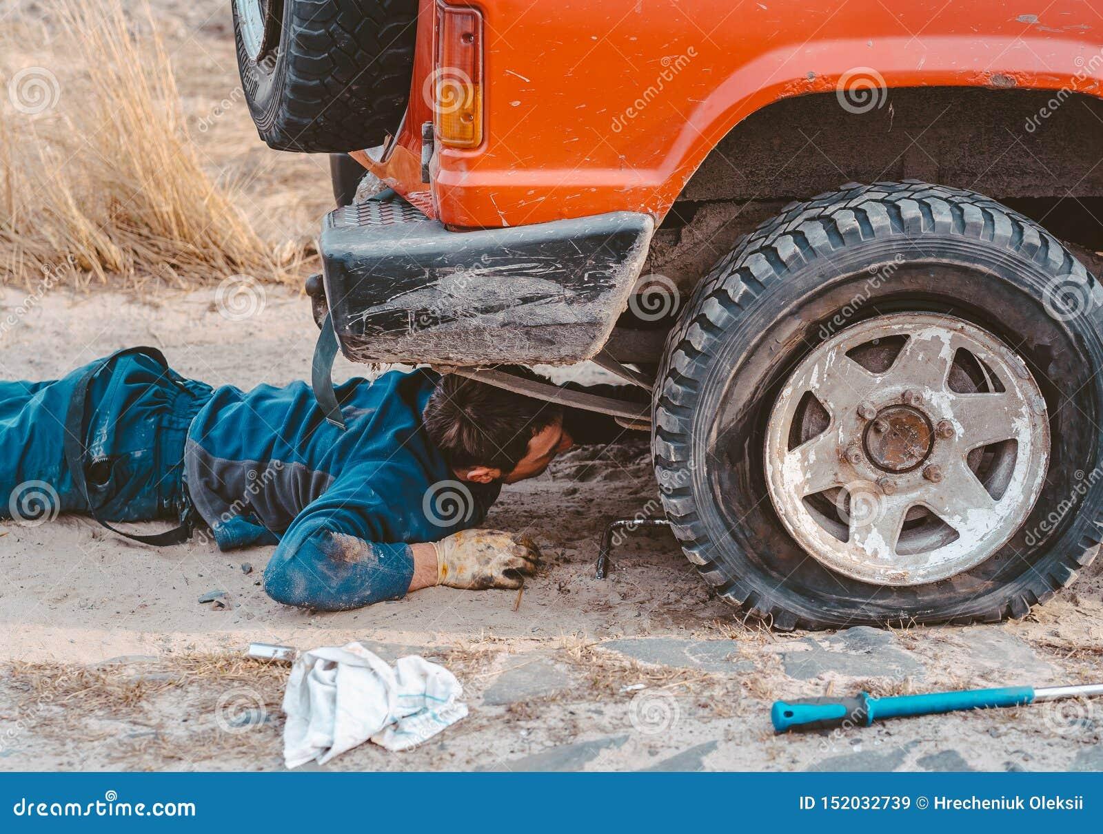 De mens ligt onder een 4x4-auto op een landweg