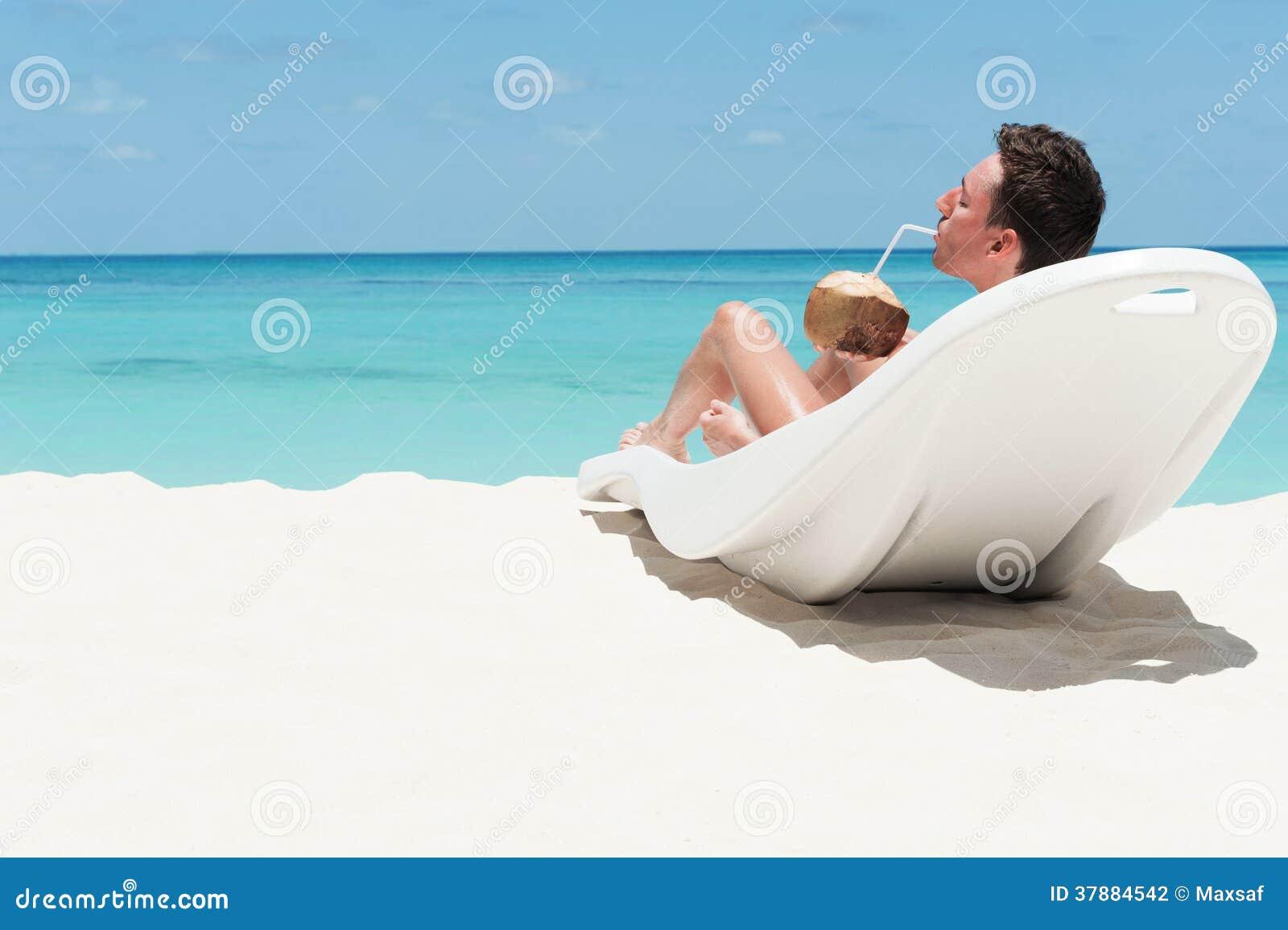 De mens ligt op lanterfanter met kokosnoot. Vrije tijdsactiviteit op strand.  Mens