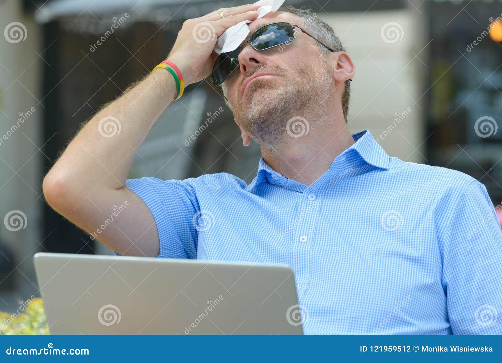 De mens lijdt aan hitte terwijl het werken met laptop