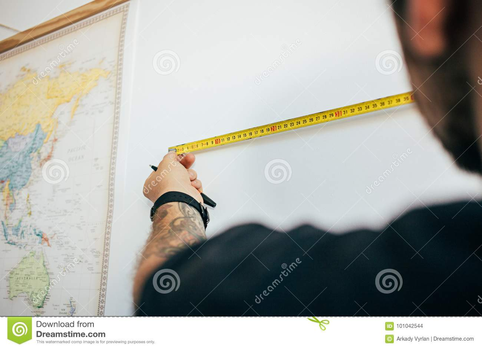 De mens meet muur met het meten van band