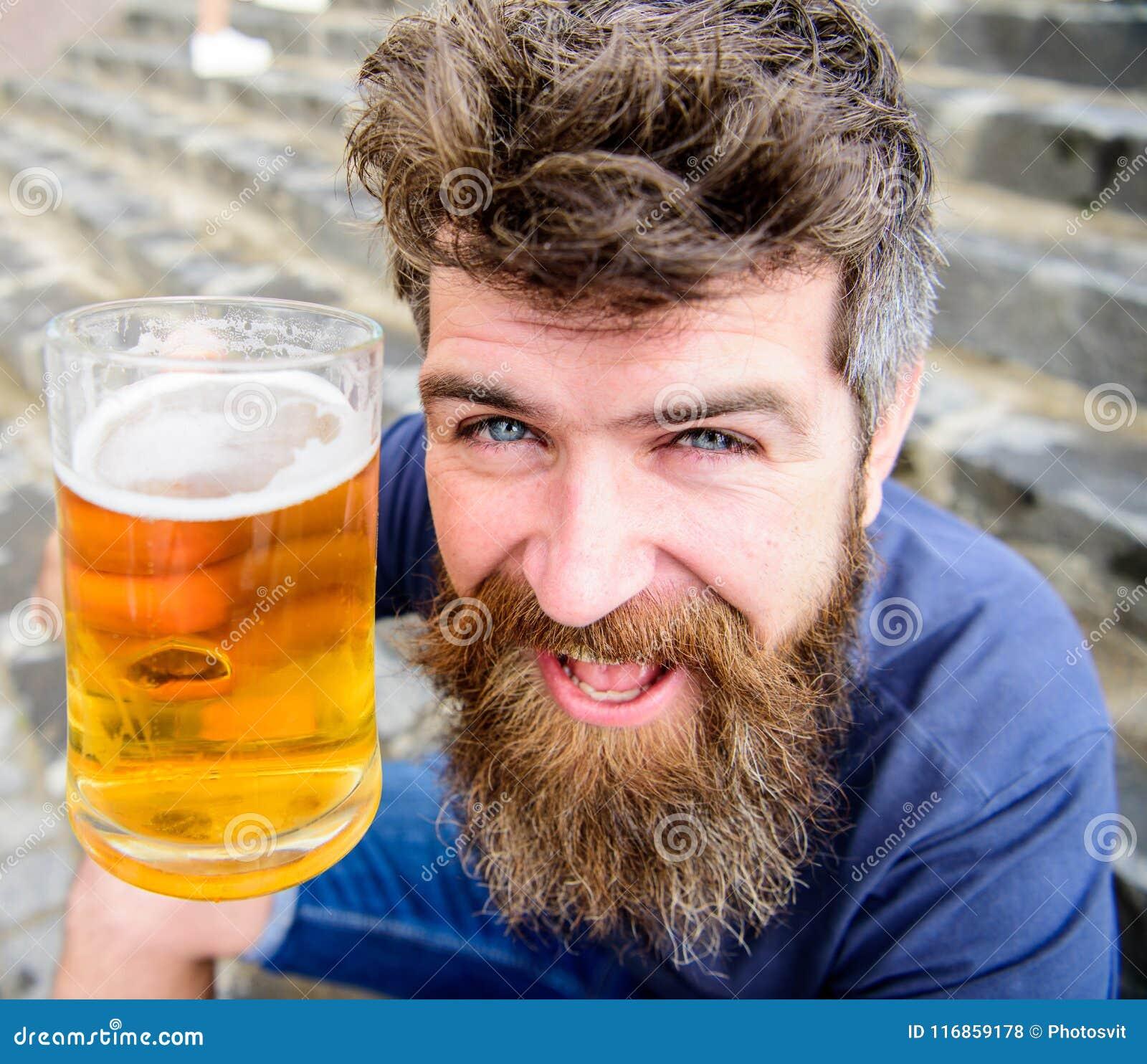 De mens met baard en snor houdt glas met bier terwijl op steentreden zit De vrijdag ontspant concept Hipster op vrolijk
