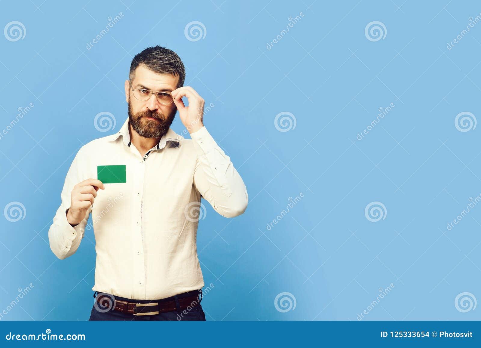 De mens met baard in wit overhemd houdt groen adreskaartje Kerel met slim die gezicht met glazen op blauwe achtergrond wordt geïs