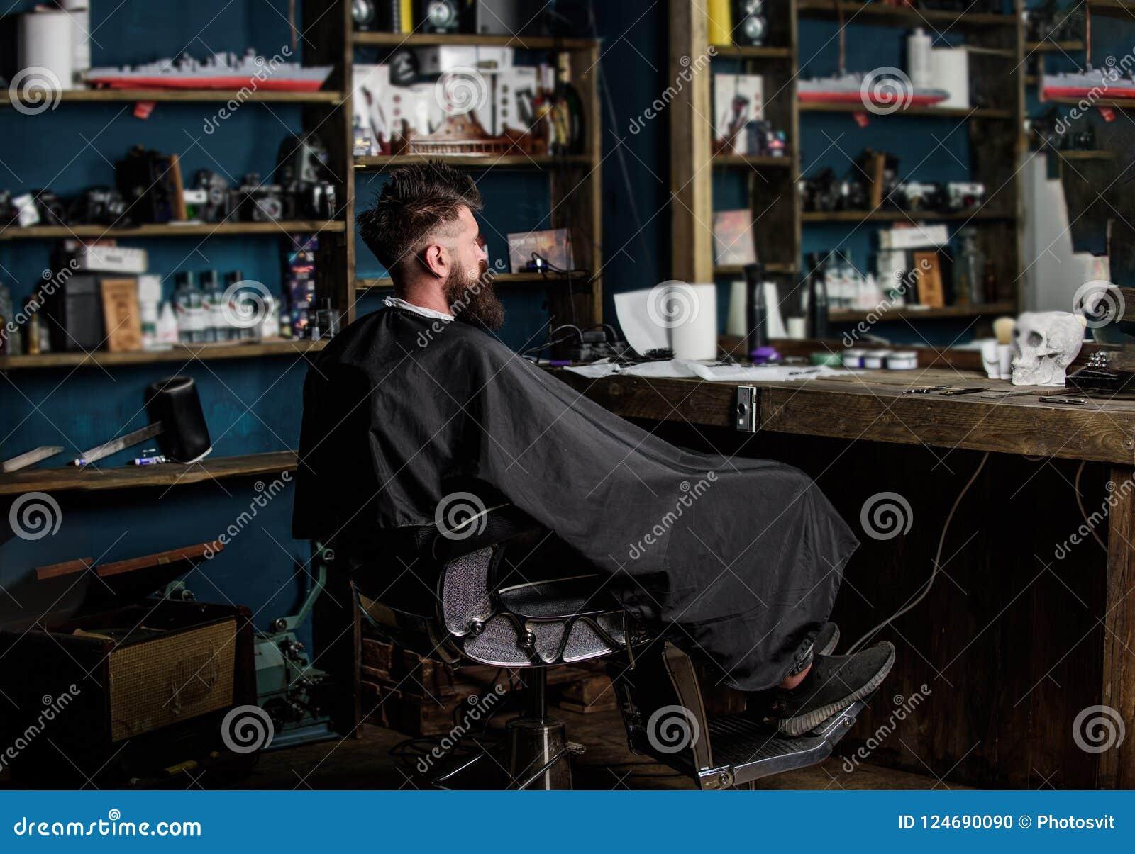 De mens met baard met zwarte kaap wordt behandeld zit als kappersvoorzitter voor spiegel die Mens met baardcliënt van hipster