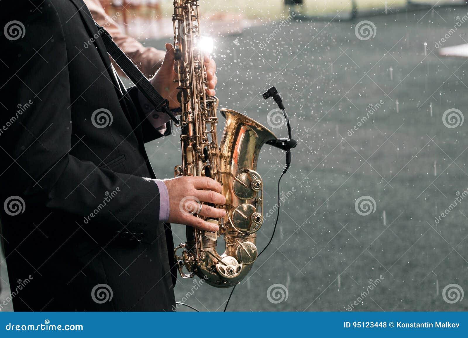 De mens met een saxofoon bevindt zich onder regen