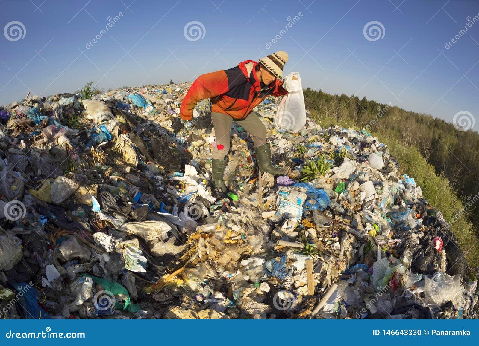 De mens met een zak neemt afval op
