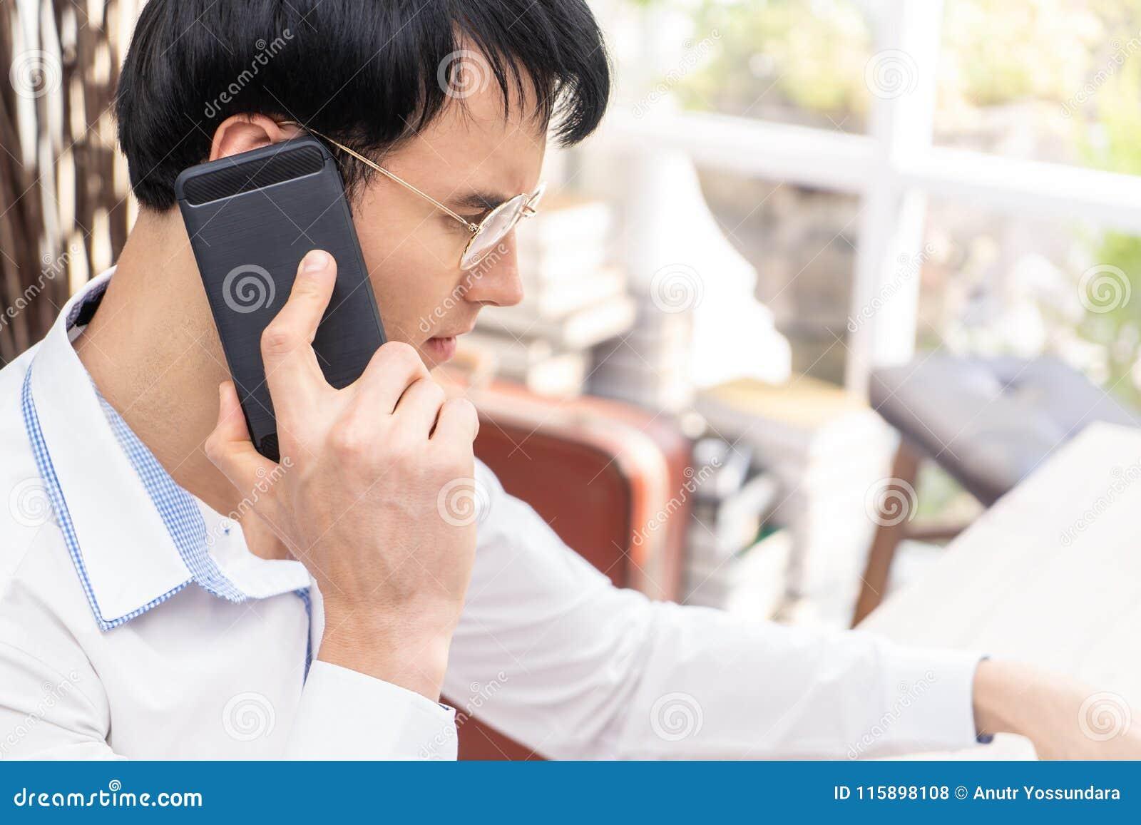 De mens met glazen die zwarte mobiele omhoog gesloten telefoon met behulp van schoot, bri