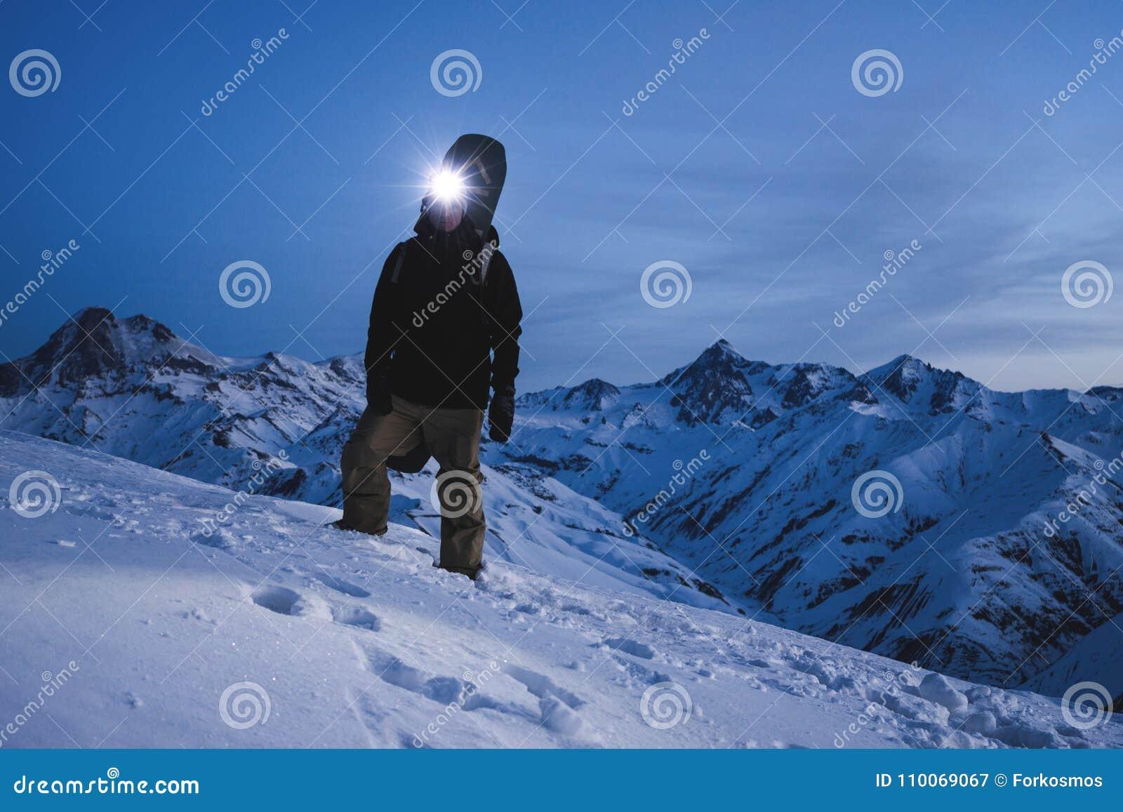 De mens met koplamp en de rugzak die ski dragen dragen status voor de verbazende mening van de de winterberg De reiziger beklimt