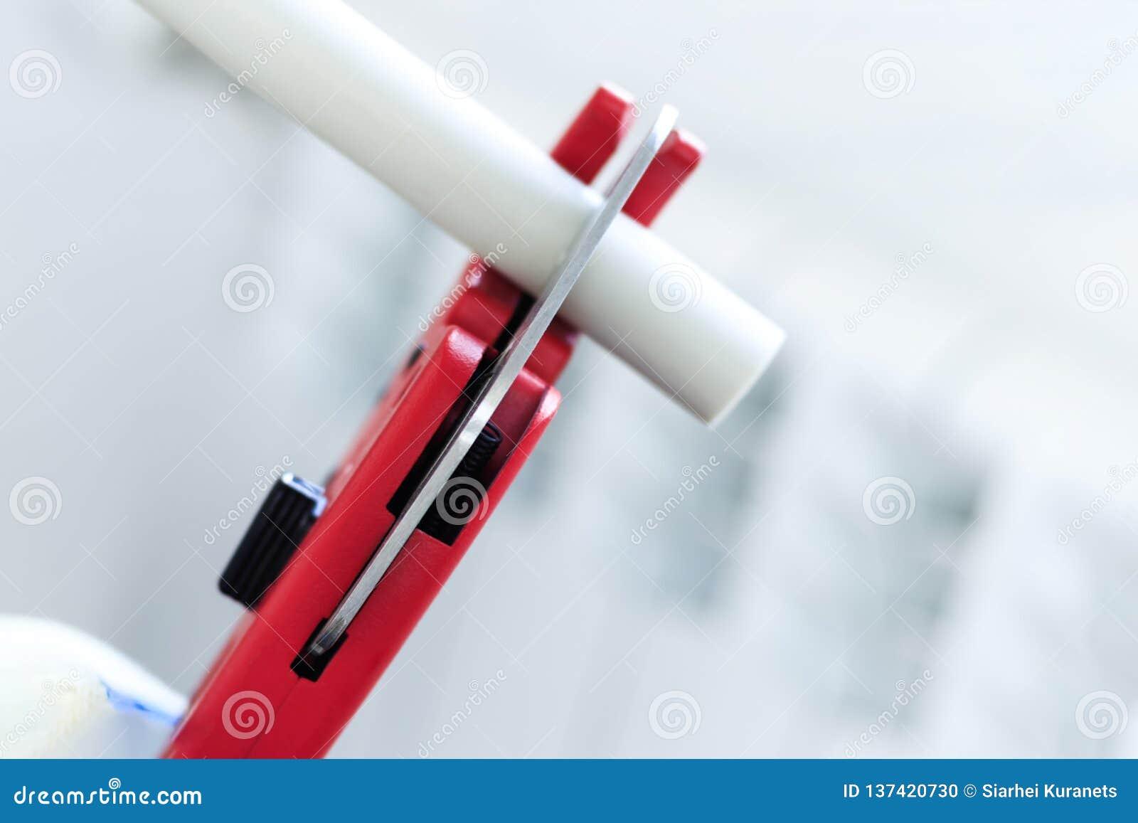 De mens met rode schaar sneed pijpen voor het verwarmen, of water polypropyleen opzettend systeem