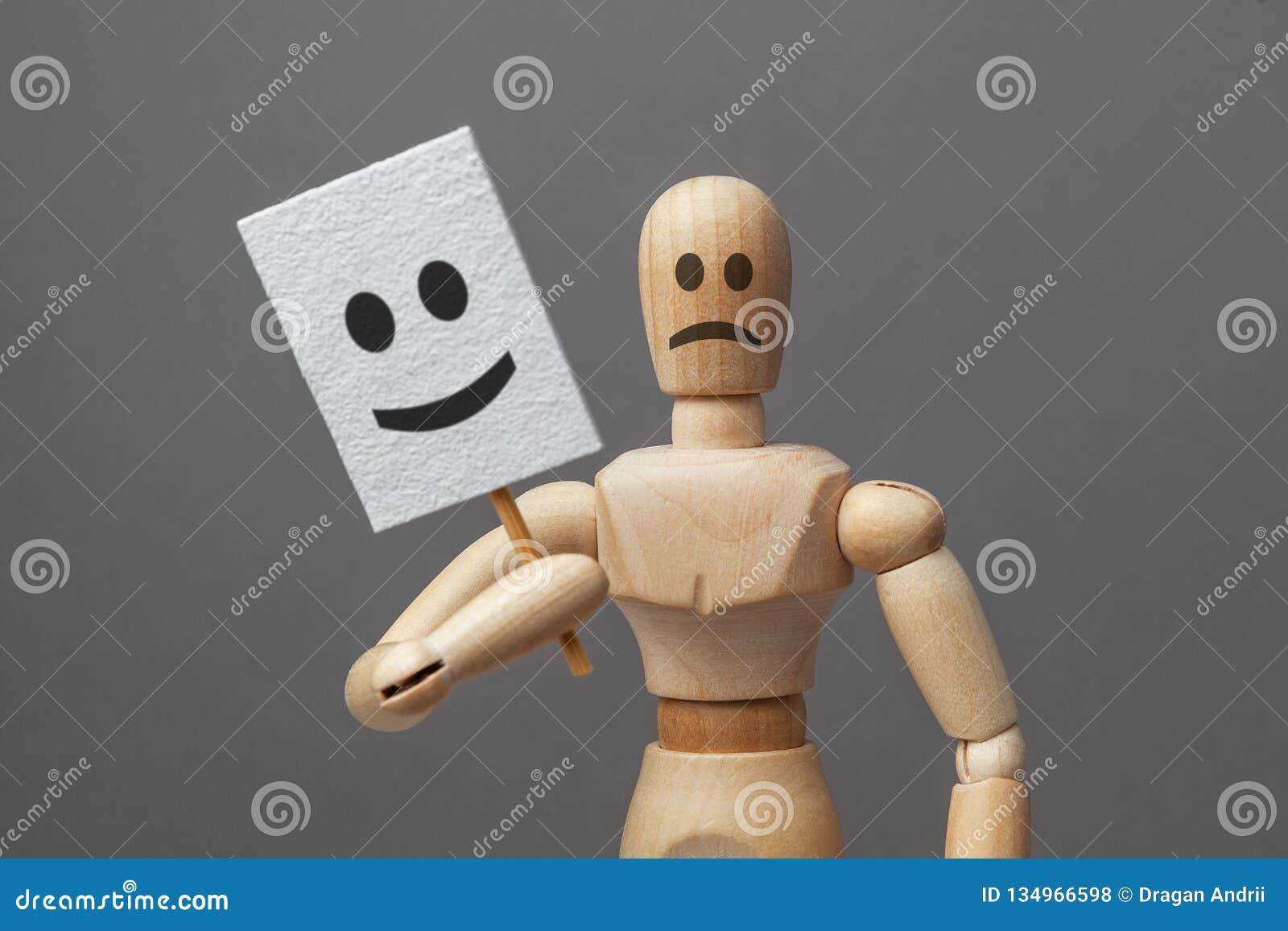 De mens met slechte kwade stemming en houdt masker van goede vrolijke stemming met glimlach schijnheiligheid