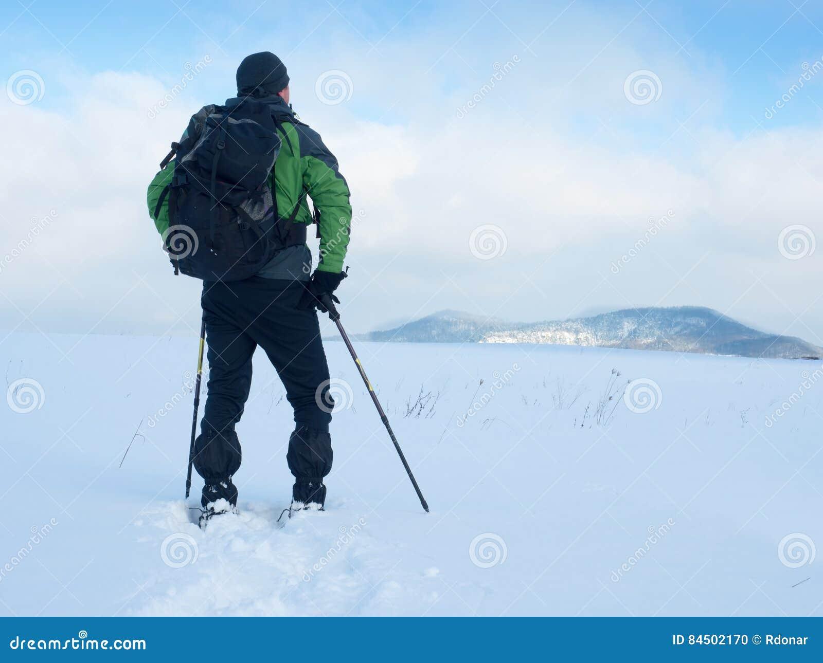 De mens met sneeuwschoenen neemt een rust in sneeuw Wandelaar het snowshoeing