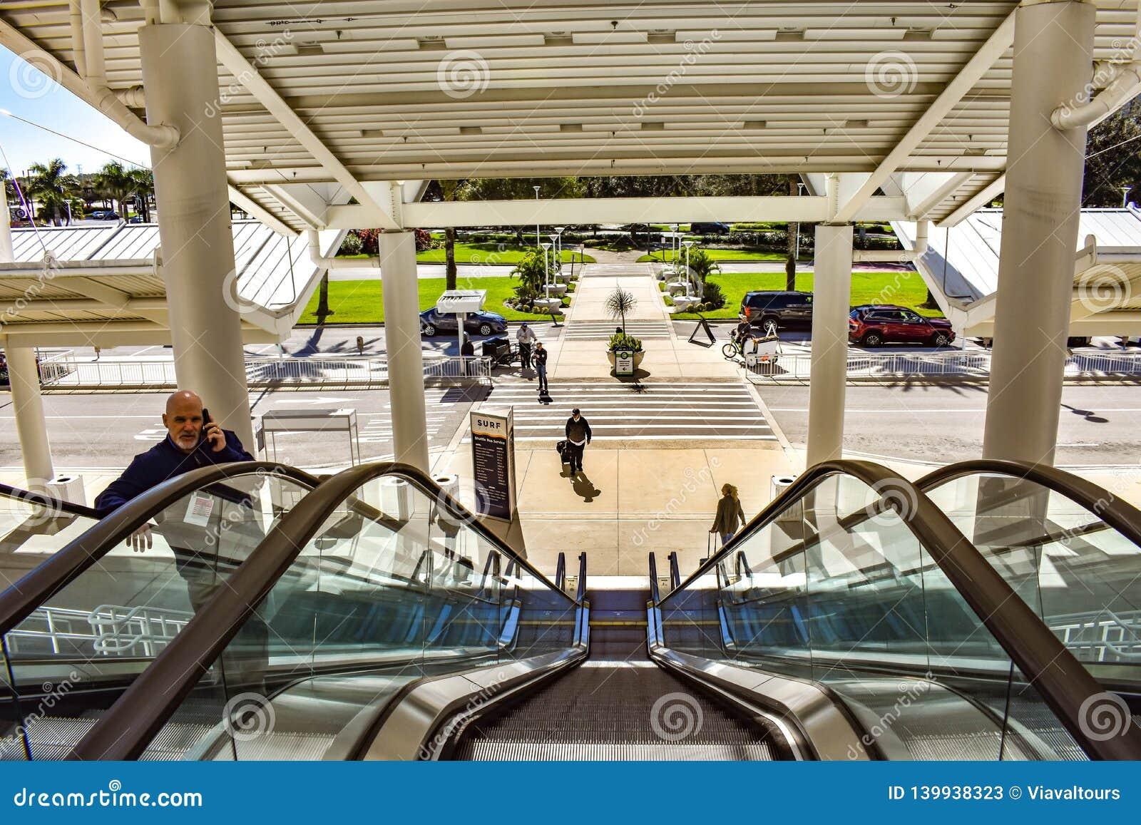 De mens neemt roltrap in hoofdingang van Orlando Convention Center bij Internationaal Aandrijvingsgebied