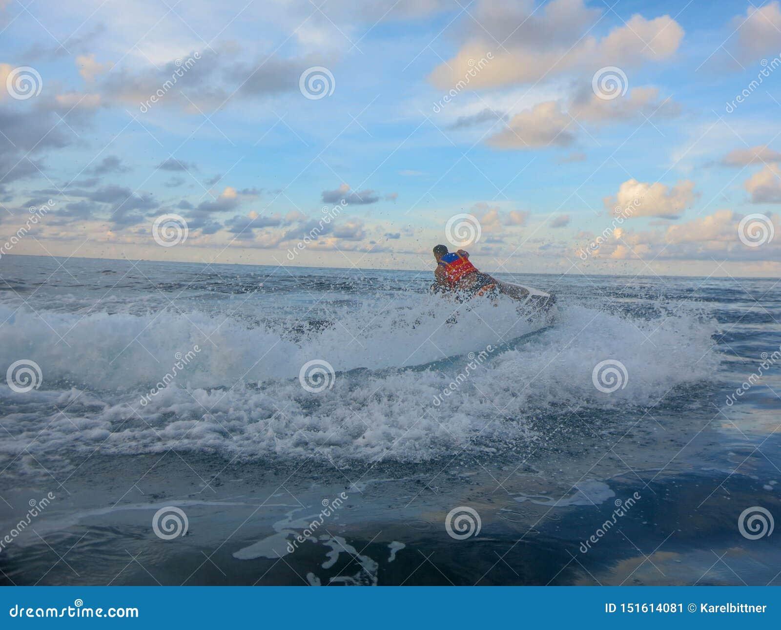 De mens op straalskidraaien met veel bespat De jongen die van de tienerleeftijd op waterautoped ski?en Jonge mens op waterscooter