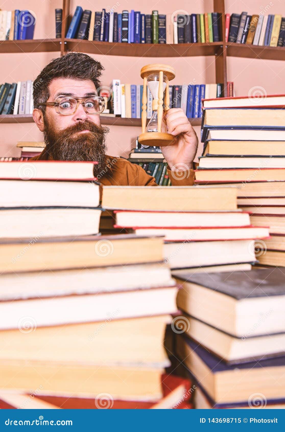De mens op verrast gezicht houdt zandloper terwijl het bestuderen, boekenrekken op achtergrond Het Concept van de tijdstroom Lera