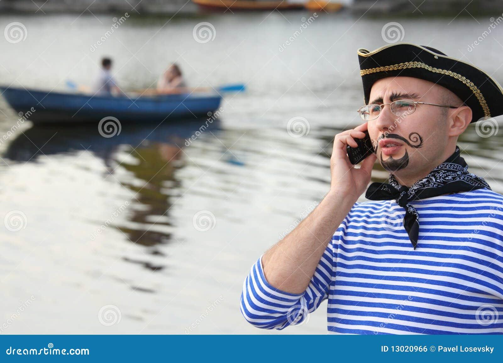 De mens in piraatkostuum spreekt door de telefoon.