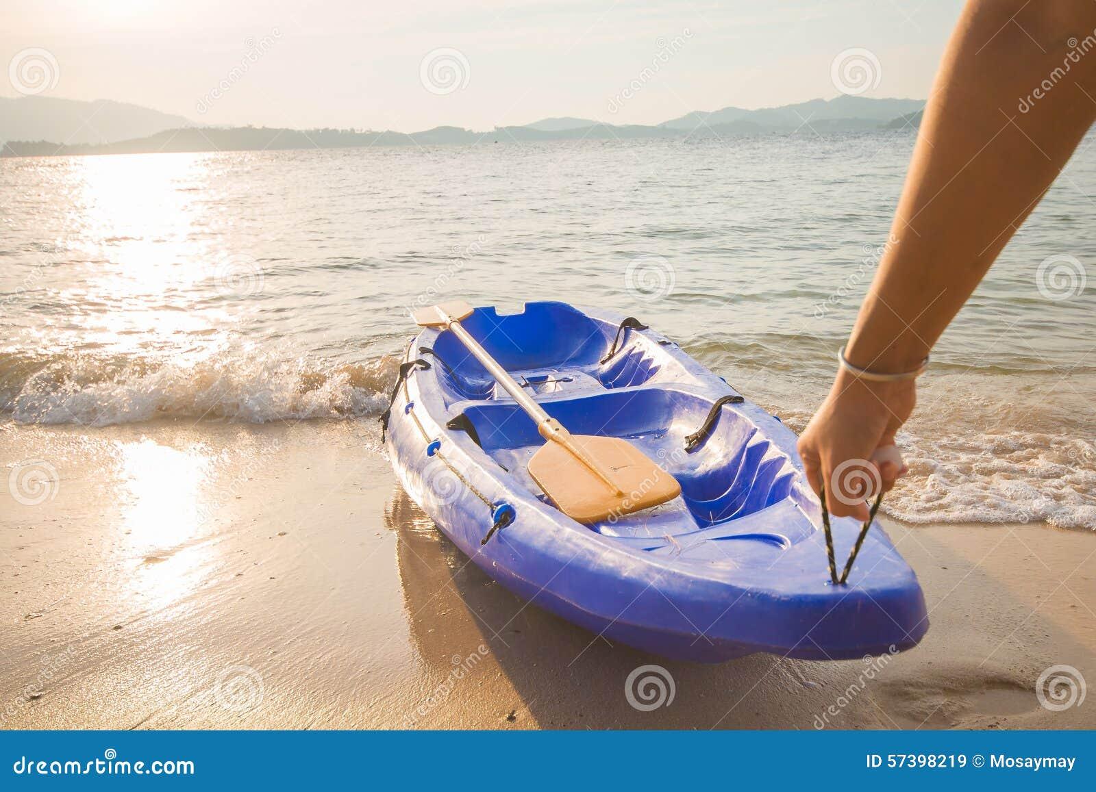 De mens sleepte omhoog de kajak op kust