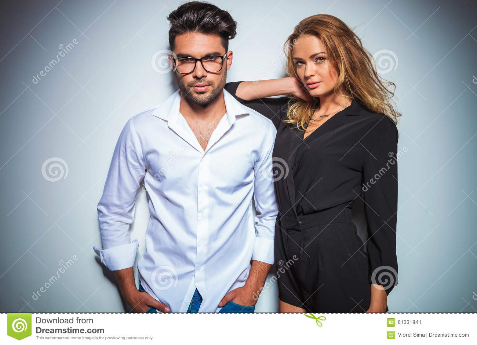 De mens stelt met indient zakken terwijl de vrouw haar wapen op van hem rust