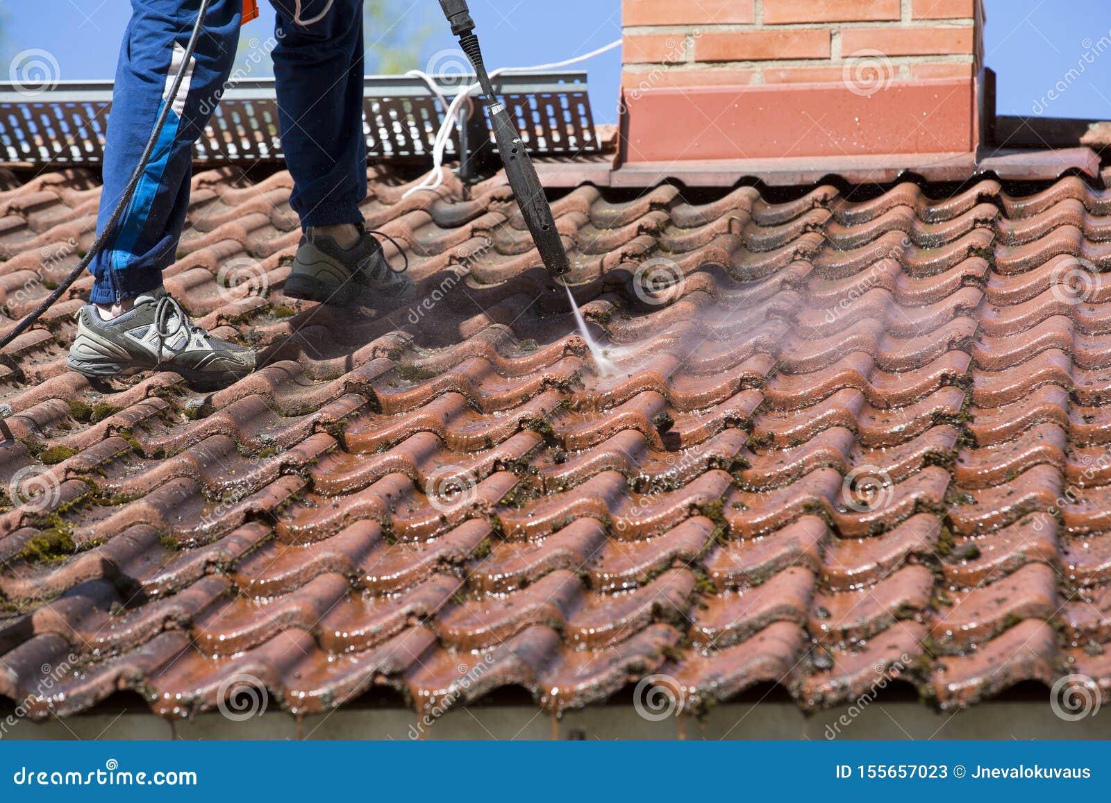 De mens wast het dak met een hoge drukwasmachine