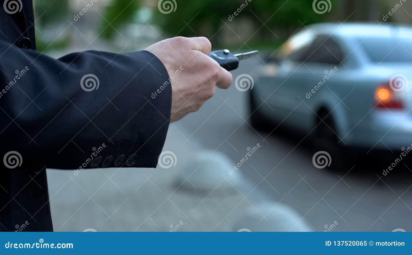 De mens zet autoalarm, veiligheidsconcept, risico om die aan auto te kapen op straat wordt geparkeerd