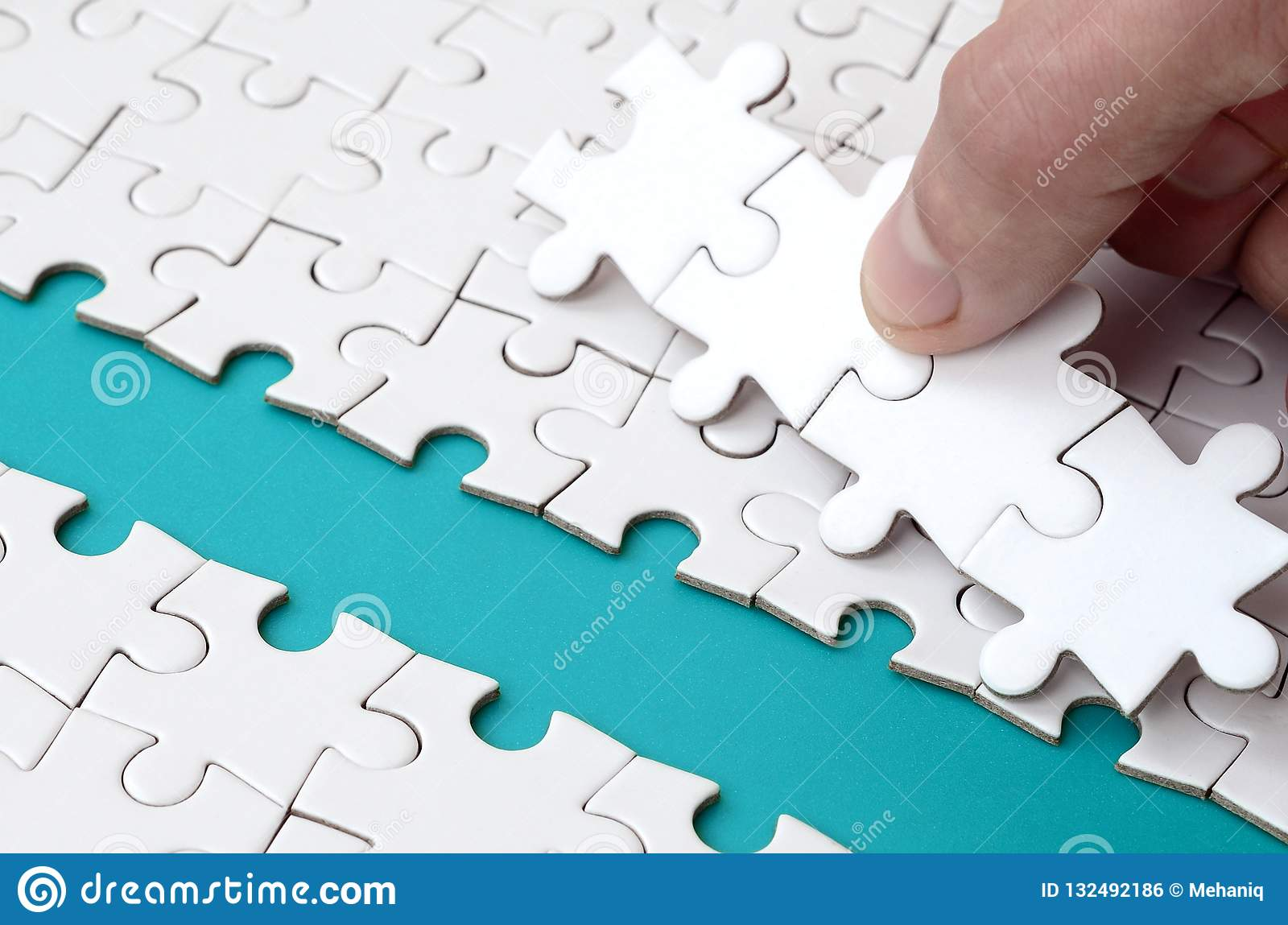 De menselijke hand baant de weg aan de oppervlakte van de puzzel, die een blauwe ruimte vormen Het concept het overwinnen van de