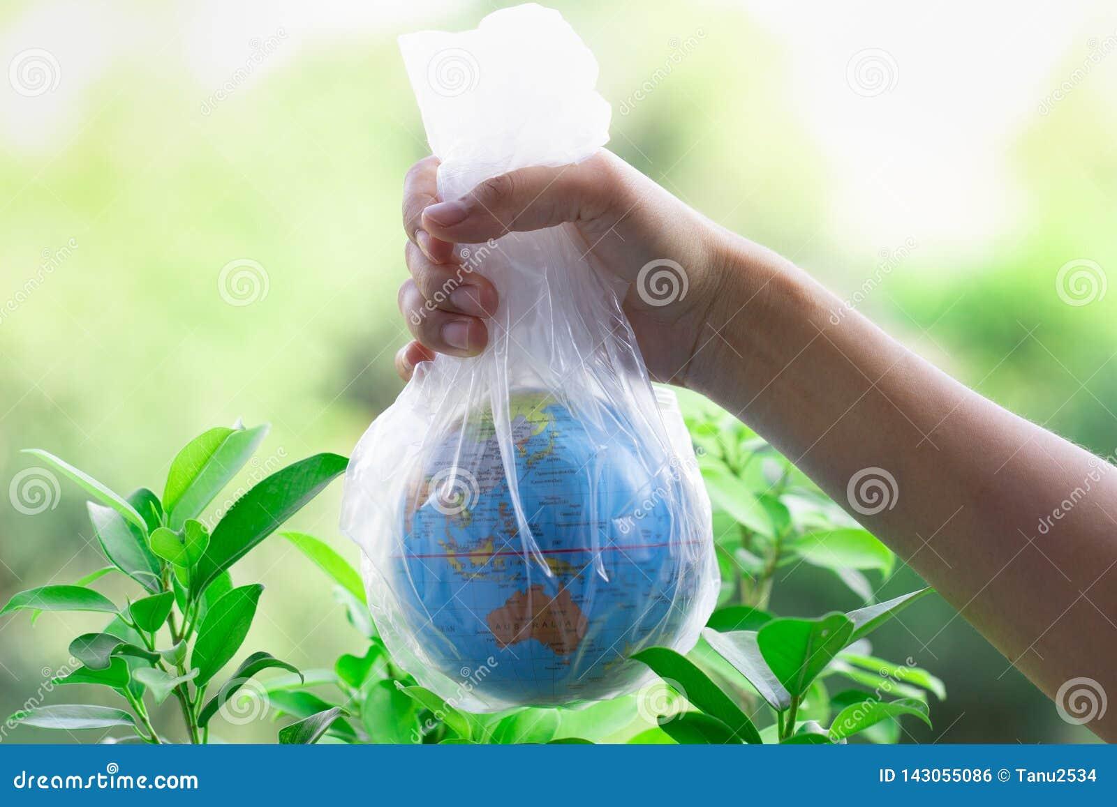 De menselijke hand houdt de aarde in een plastic zak