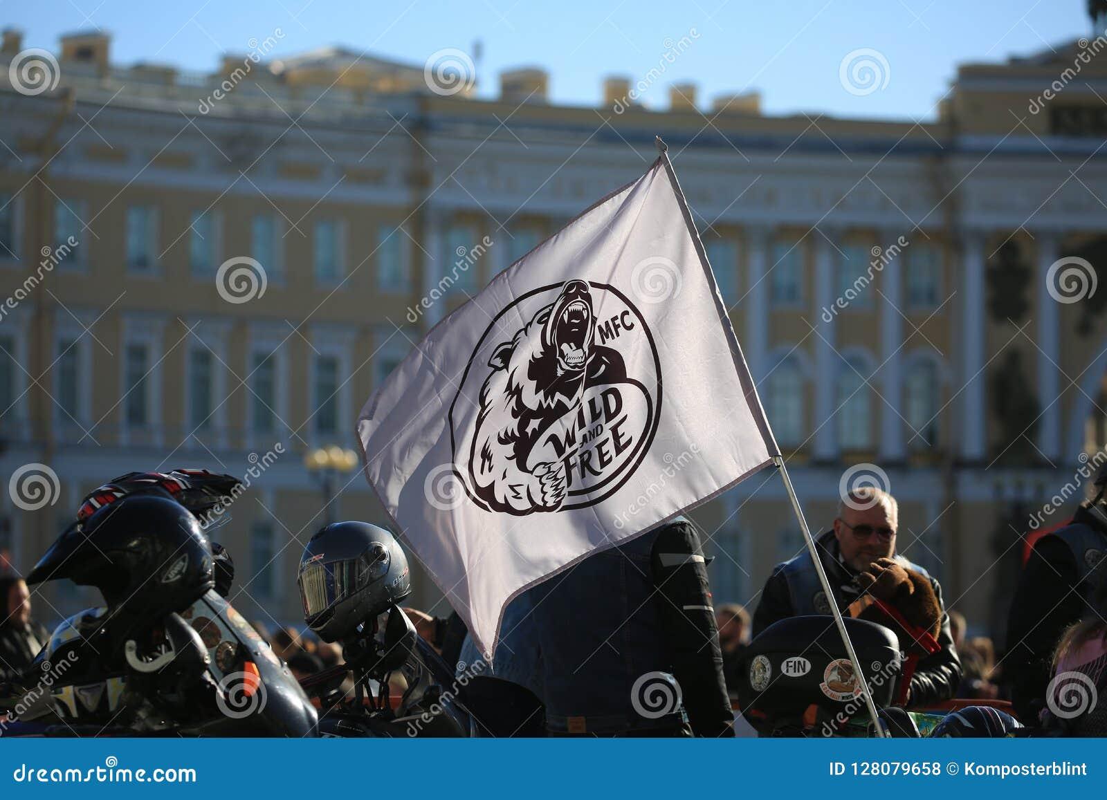 De mensen en de vlag van Wilde en Vrije moto fanats knuppelen tegen de achtergrond van het Algemene Personeelsgebouw