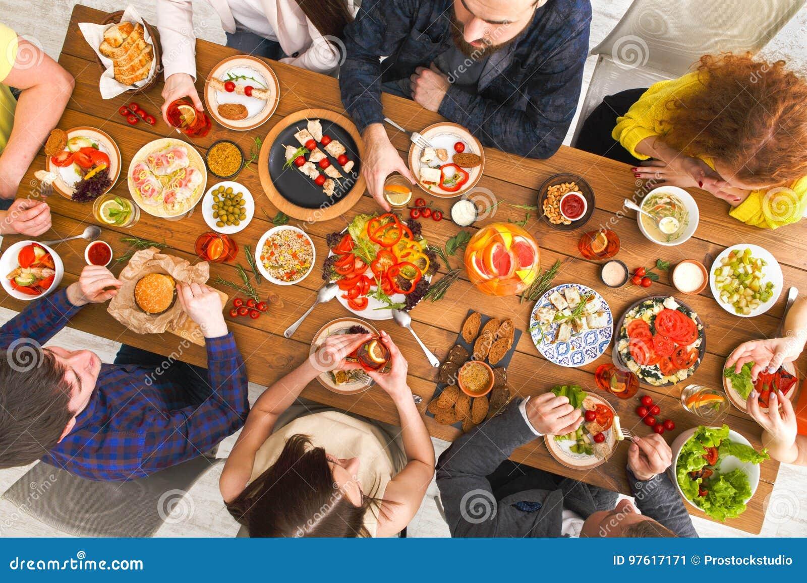 De mensen eten gezonde maaltijd bij de gediende partij van het lijstdiner