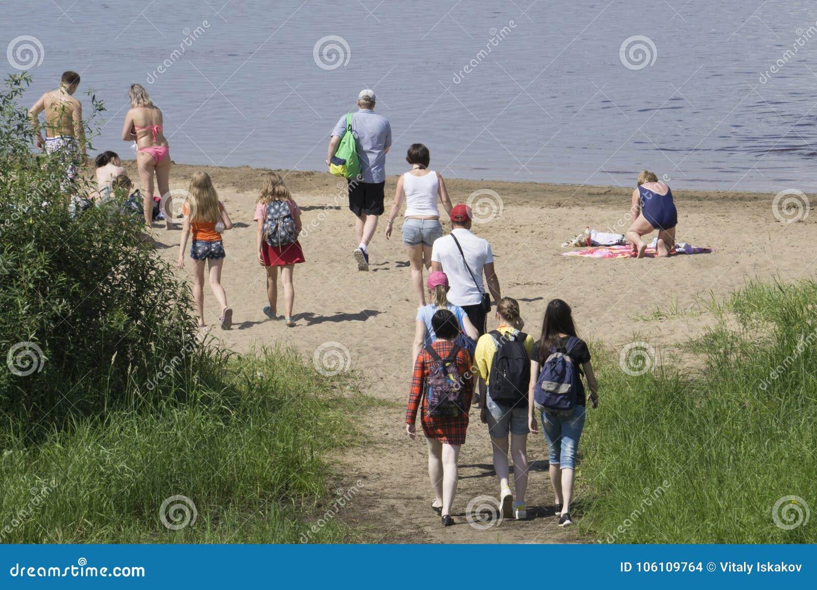 De mensen gaan naar het strand zonnebaden