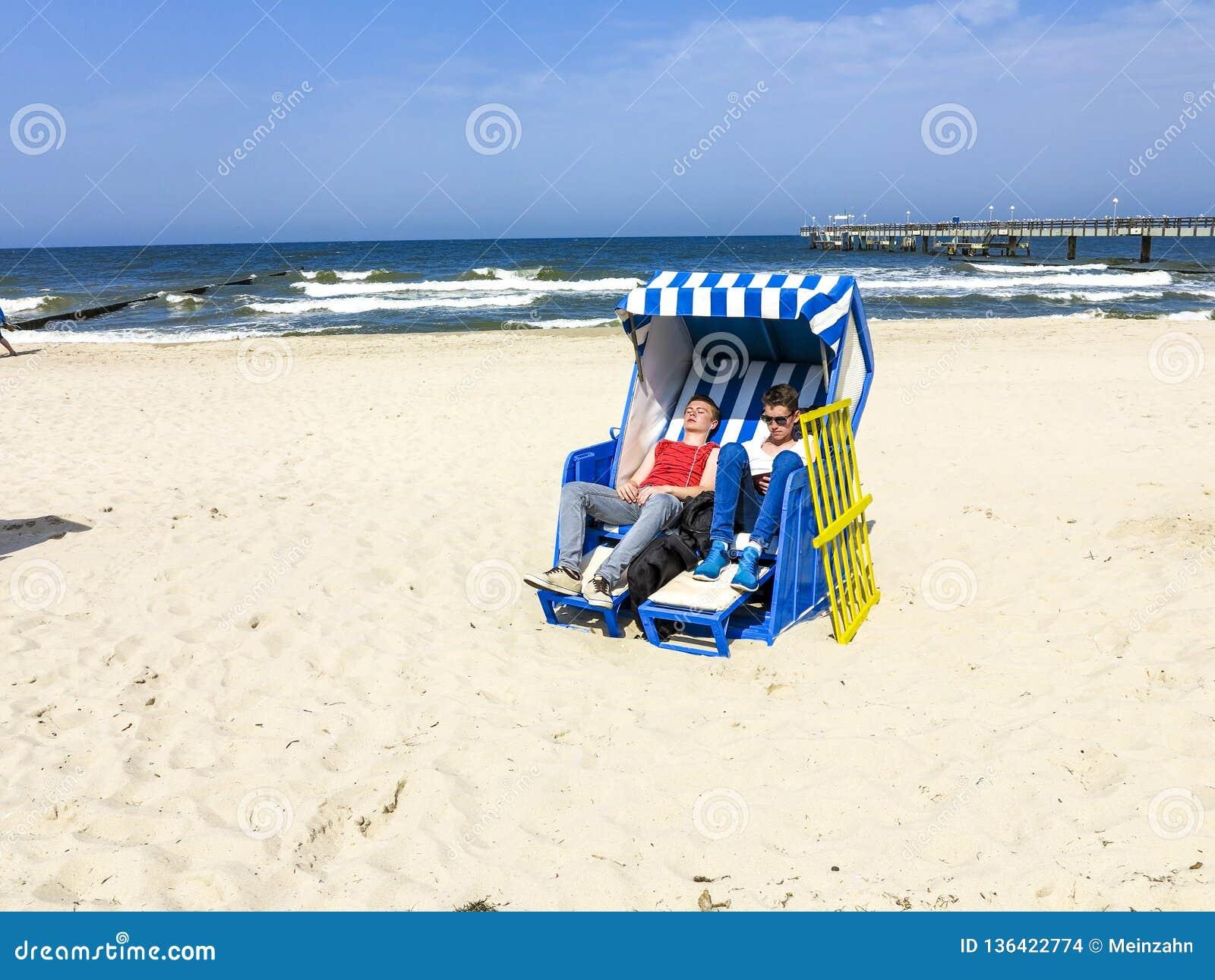 De mensen genieten van sunbath in roofed rieten ligstoel
