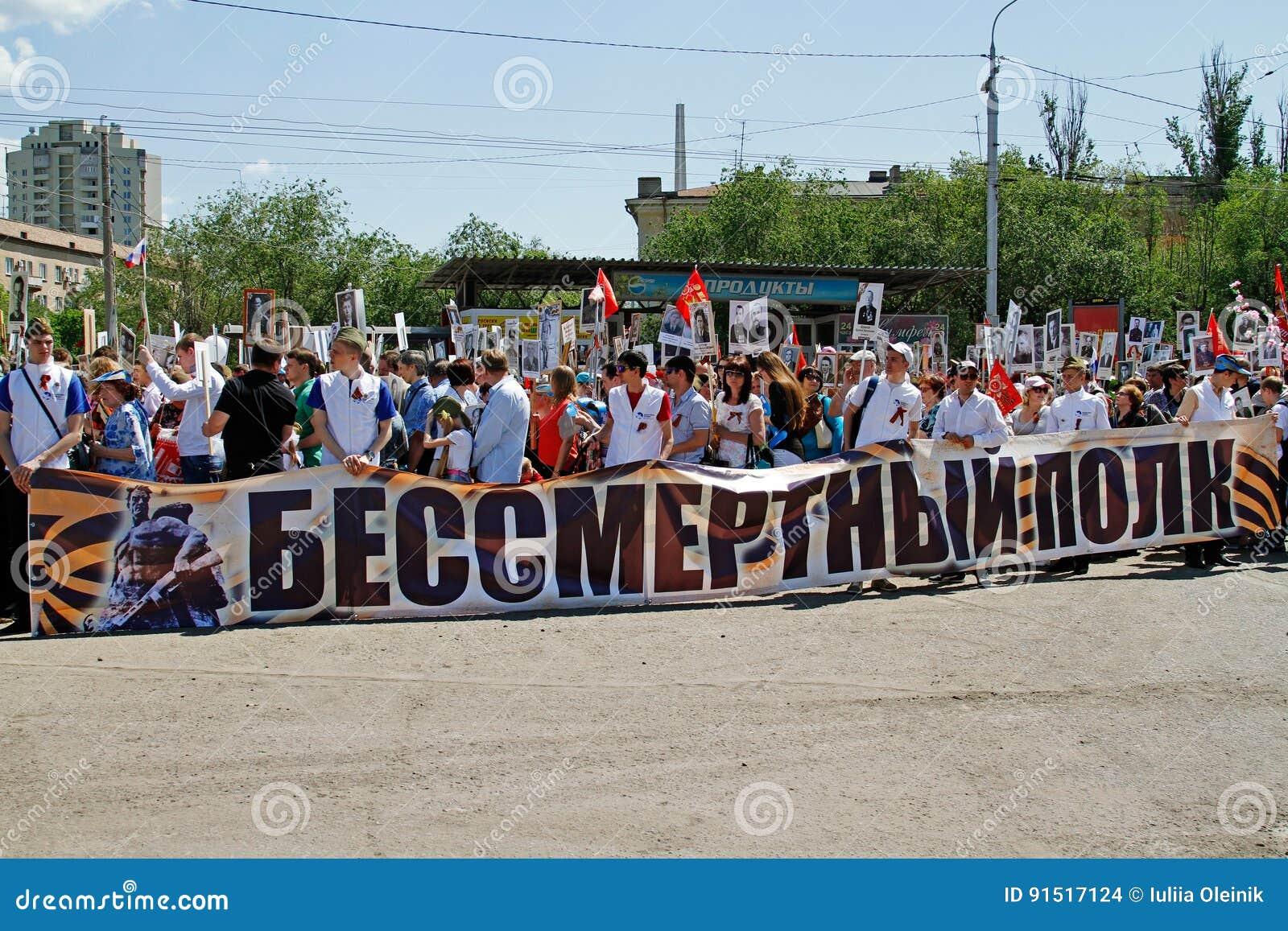 De mensen houden banner van Onsterfelijk regiment en portretten van hun verwanten op Overwinningsdag in Volgograd