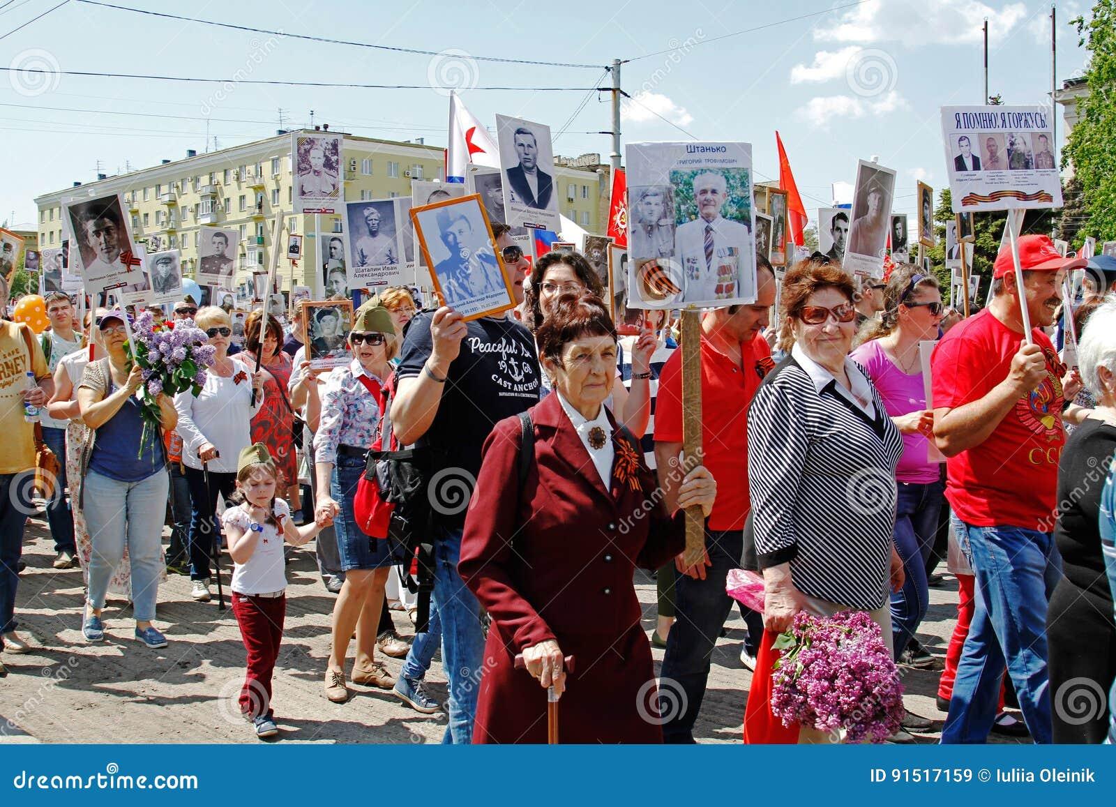 De mensen houden portretten van hun verwanten in het actie` Onsterfelijke regiment ` op Overwinningsdag in Volgograd
