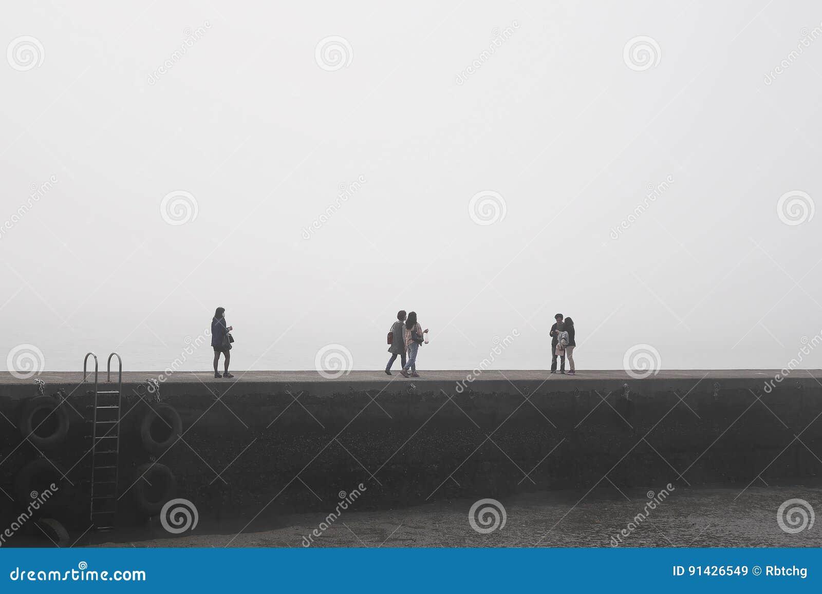 De mensen liepen doelloos met geheimzinnige mist op de steiger bij haven