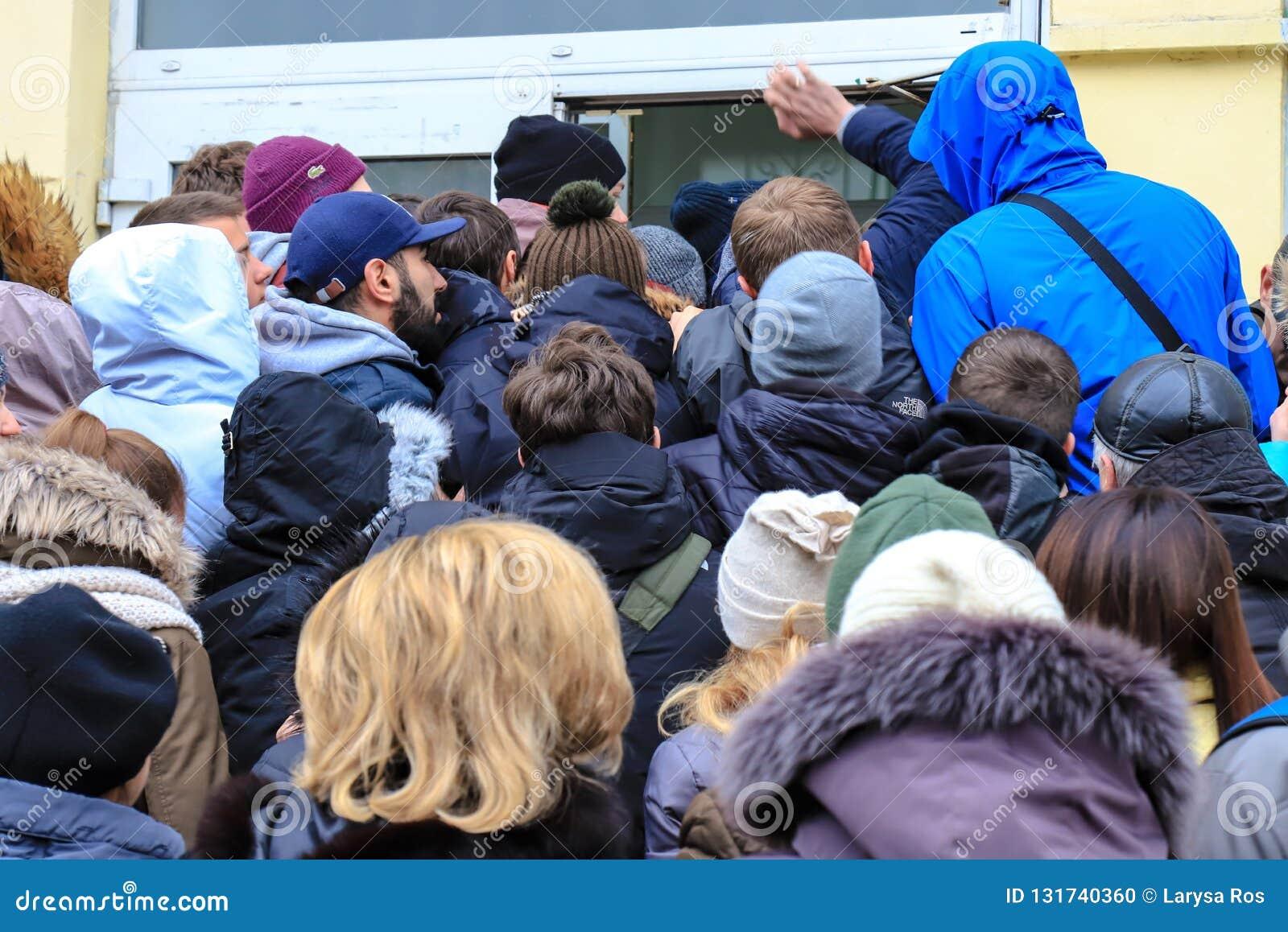 De mensen overbevolken dichtbij de opslag tijdens de verkoop De klanten gaan de wandelgalerij op Black Friday in