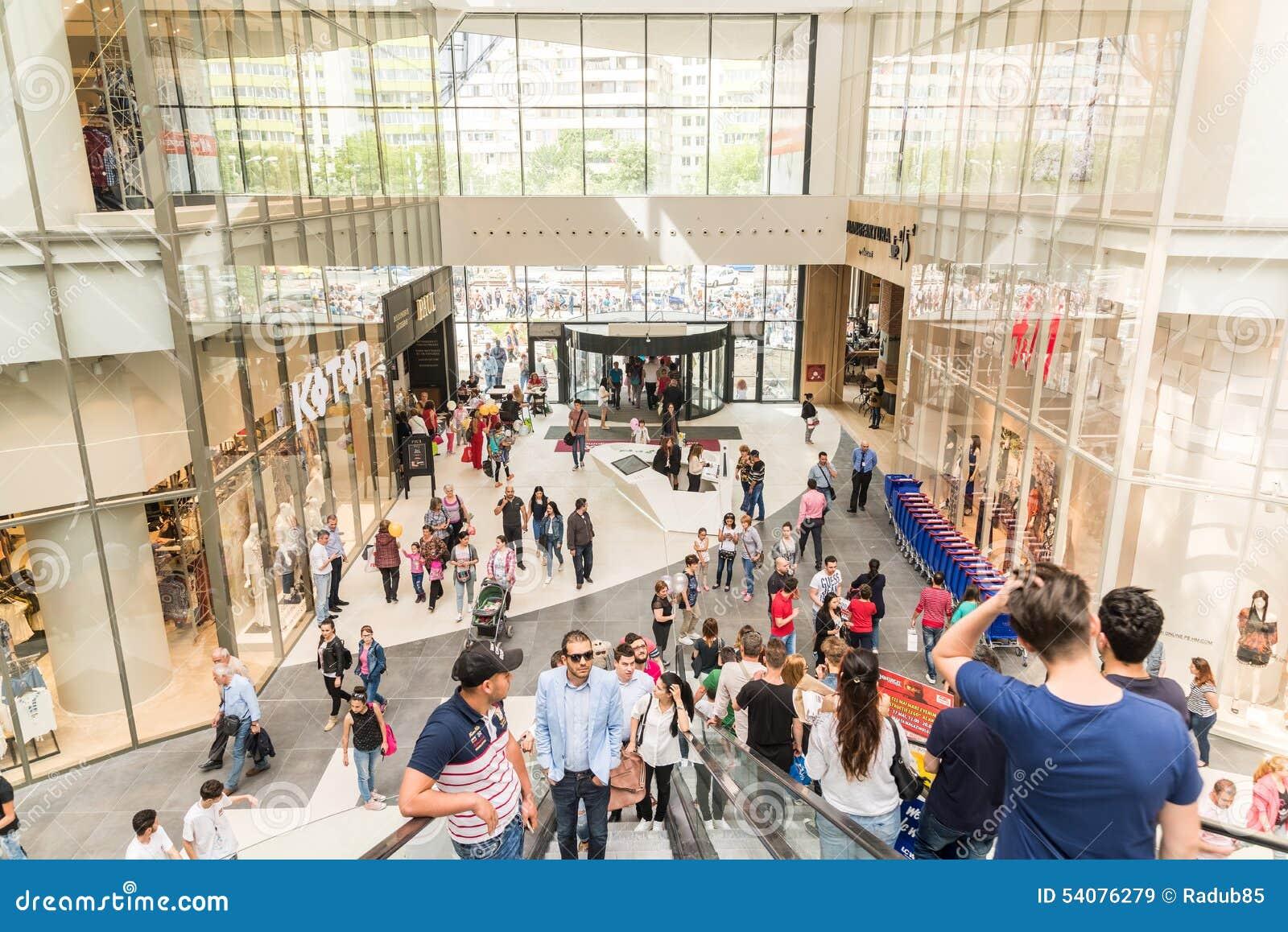 De mensen overbevolken op Roltrappen in Luxewinkelcomplex