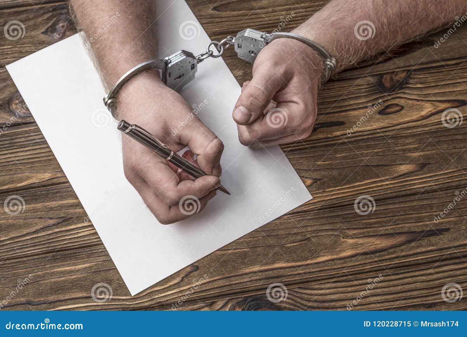 De mensen` s handen met handcuffs vullen het strafblad, bekentenis