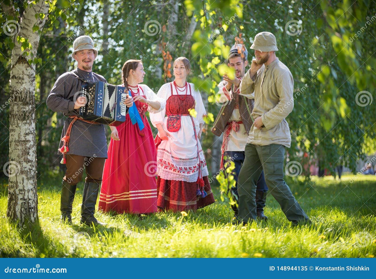 De mensen in traditionele Russische kleren bevinden zich in het hout en het spreken - ??n van hen spelen de harmonika en
