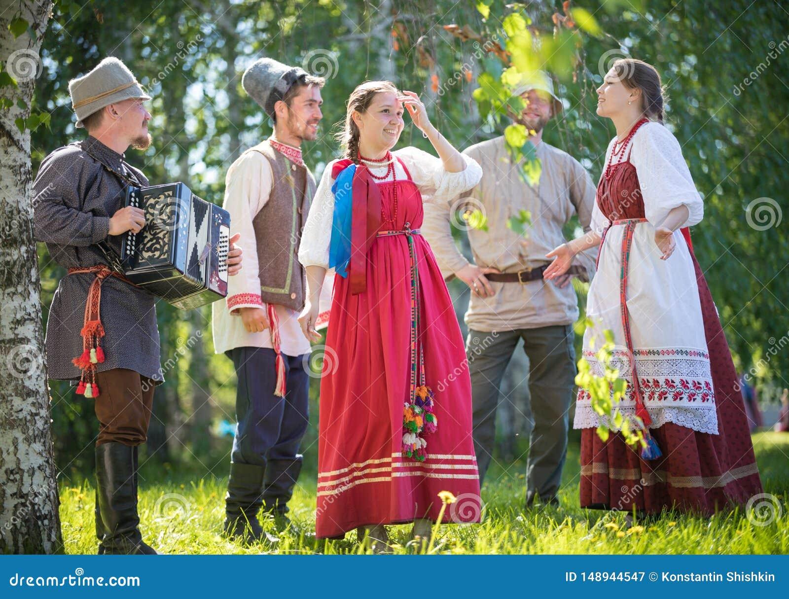 De mensen in traditionele Russische kleren communiceren in het bos op de weide - ??n van hen spelenmuziek op harmonika