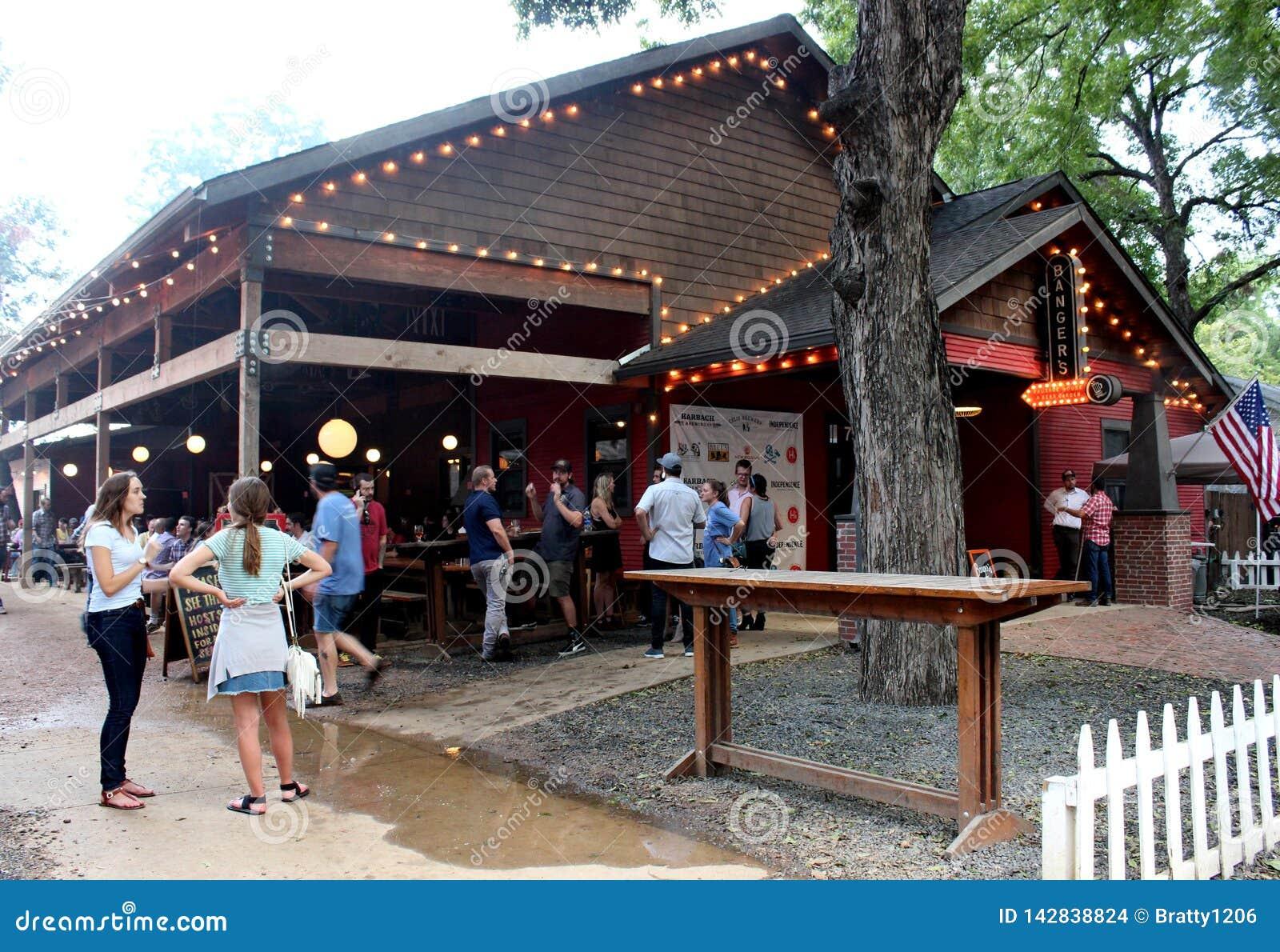 De mensen verzamelden zich binnen op gronden van populaire aantrekkelijkheid, de Worsthuis van Banger en Biertuin, Austin, Texas,